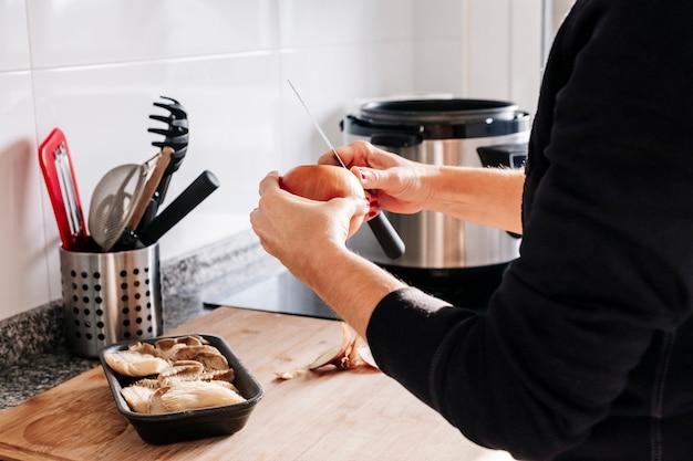 Ręce kobiety obieranie cebuli w kuchni.