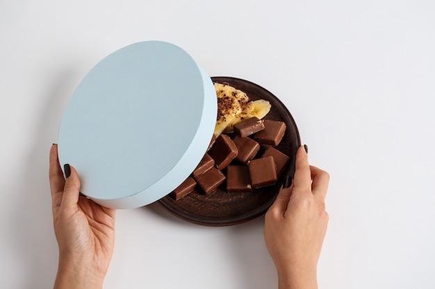 Ręce kobiety otwierając pudełko z czekoladą i bananem na białym tle