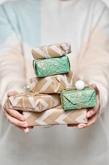 Ręce kobiety posiadają pudełka na prezenty. ozdobione pudełko na boże narodzenie lub nowy rok.