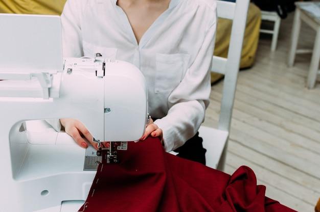 Ręce kobiety pracującej na zbliżeniu maszyny do szycia. krawiectwo koncepcyjne i projektowanie odzieży.