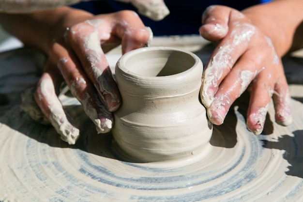 Ręce kobiety pracy ceramiki na kole garncarskim