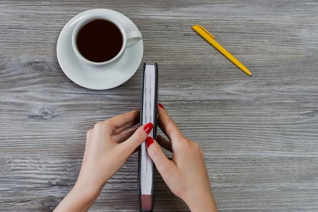 Ręce Kobiety Próbują Otworzyć Zamkniętą Księgę. Filiżanka Kawy, Długopis Są W Tle. Widok Z Góry Premium Zdjęcia