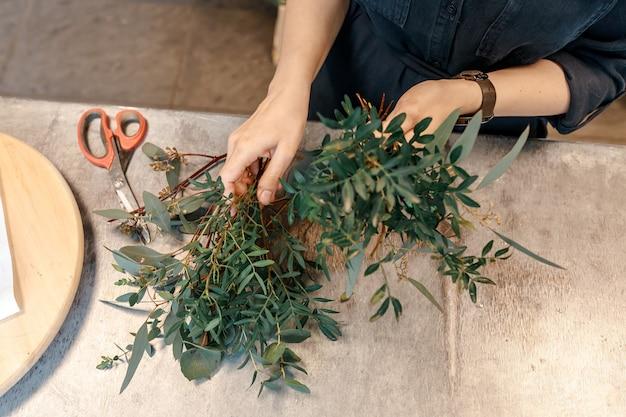 Ręce kobiety przygotowują zielone rośliny na bukiet kwiatów. nożyce. koncepcja prezentów własnymi rękami.