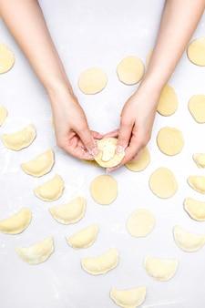 Ręce kobiety robią ravioli