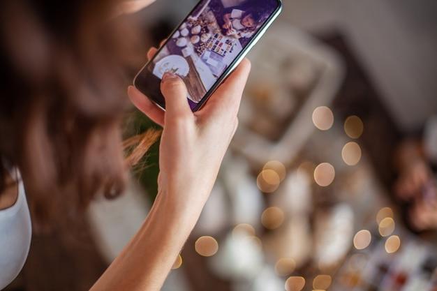 Ręce kobiety robią zdjęcia telefonem świąteczna kompozycja z ręcznie robioną choinką