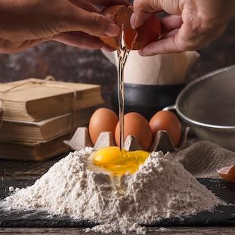 Ręce kobiety rozbijają jajko na mąkę. zbliżenie