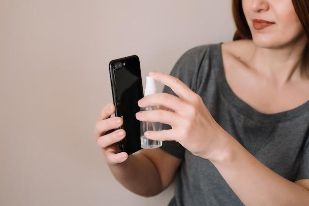 Ręce kobiety rozpylają środek dezynfekujący na telefon komórkowy w celu czyszczenia i ochrony przed wirusami
