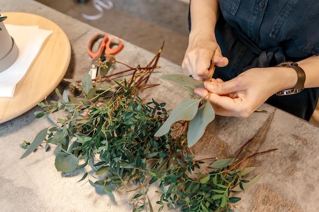 Ręce kobiety ścinają rośliny, przygotowując je do stworzenia kompozycji kwiatowej w pudełku. koncepcja prezent kwiat.