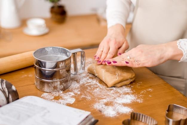Ręce kobiety toczą ciasto. symbol ochrony, komfort cieplny.