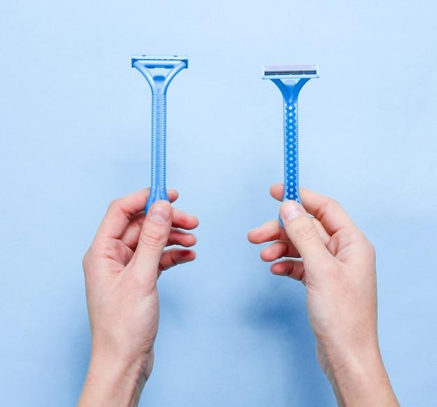 Ręce kobiety trzymają dwie maszynki do golenia do depilacji na niebieskim tle