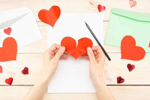 Ręce kobiety trzymają podarte czerwone serce papieru. utrata miłości, wiadomości, listu