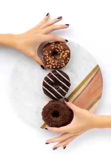 Ręce kobiety, trzymając czekoladowy pączek na białej powierzchni