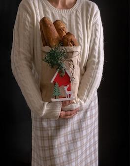 Ręce kobiety trzymając torbę na zakupy z chlebem na wakacje nowy rok lub boże narodzenie