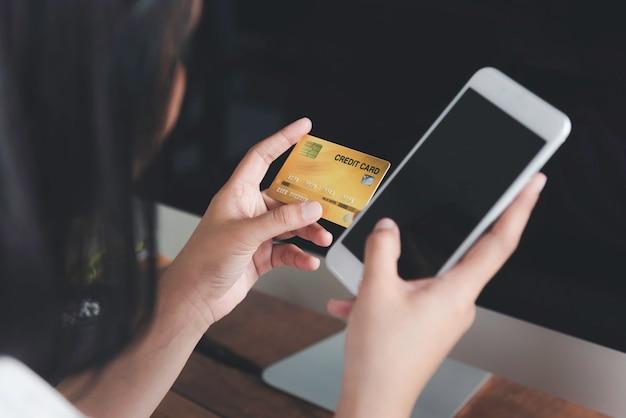 Ręce kobiety trzymającej kartę kredytową i używającej smartfona do zakupów online lub e-commerce