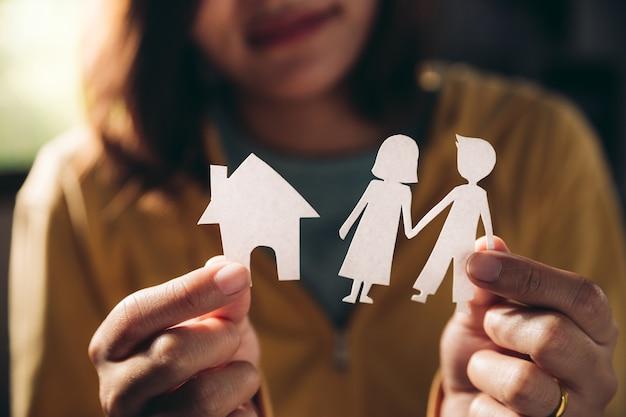 Ręce kobiety trzymającej para papieru i mały domek w koncepcji relacji pokój dzienny, rodzina i ludzie.