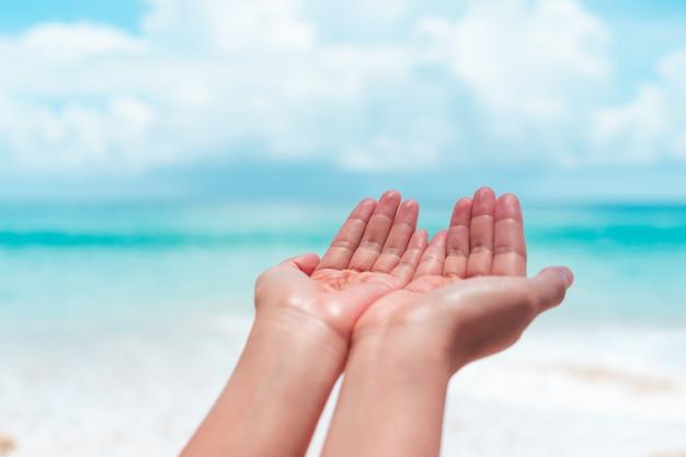 Ręce kobiety układają się razem jak modlitwa przed czystą plażą i błękitnym niebem.