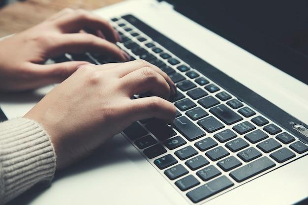 Ręce kobiety używające i piszące na klawiaturze laptopa