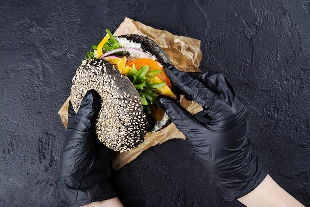 Ręce kobiety w czarnych gumowych rękawiczkach trzymają soczysty czarny kok burger