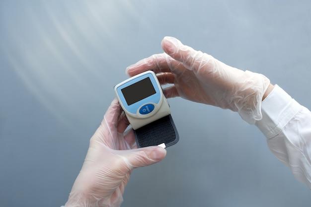 Ręce kobiety w rękawiczkach medycznych trzymają ciśnieniomierz. koncepcja lekarza medycyny opieki zdrowotnej. makieta.