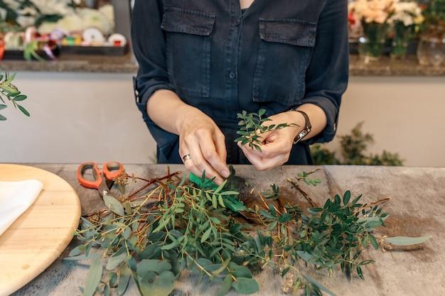 Ręce kobiety wycinają zielone rośliny, przygotowując je do stworzenia kompozycji kwiatowej w pudełku. koncepcja prezent pole kwiaty.