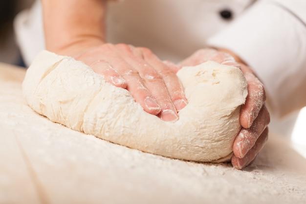 Ręce kobiety wyrabiają ciasto z bliska