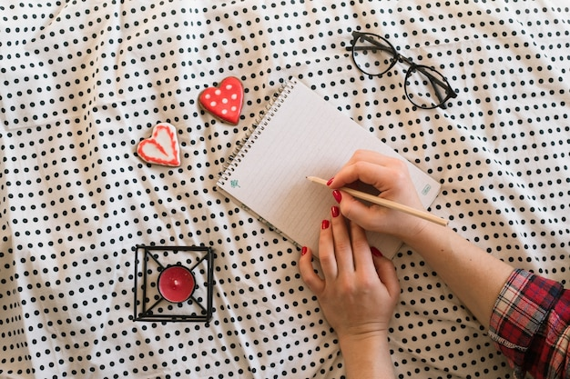 Ręce kobiety z doskonałym manicure, trzymając ołówek i notatnik spirali