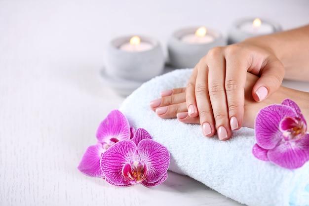 Ręce kobiety z francuskim manicure i kwiatami orchidei na drewnianym stole zbliżenie