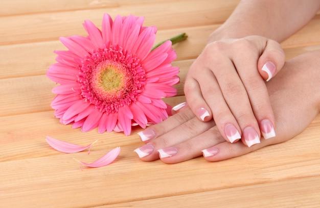 Ręce kobiety z francuskim manicure i kwiatem na drewnianym stole