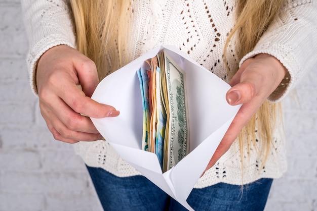 Ręce kobiety z kopertą pełną banknotów dolara i euro