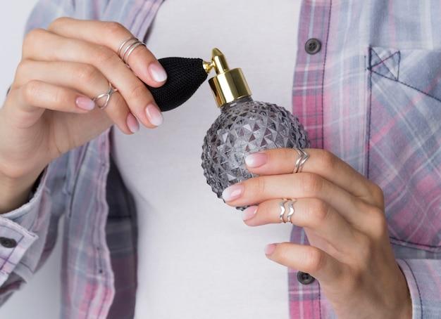 Ręce kobiety z manicure trzyma butelkę perfum vintage