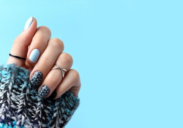 Ręce kobiety z manicure w sweter z dzianiny wełnianej