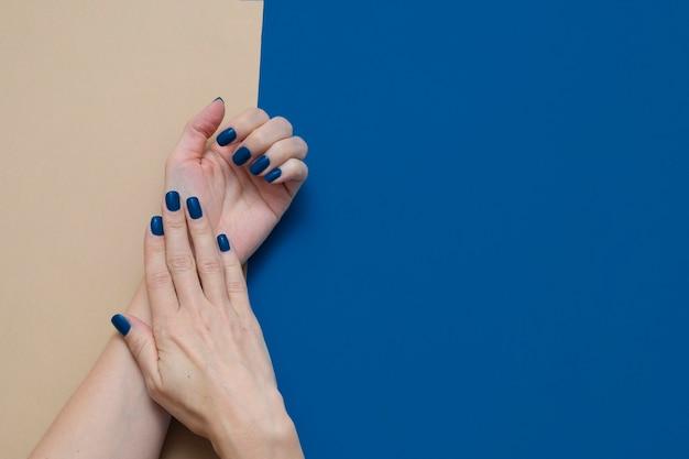 Ręce kobiety z modnymi niebieskimi paznokciami na geometrycznym niebieskim i beżowym
