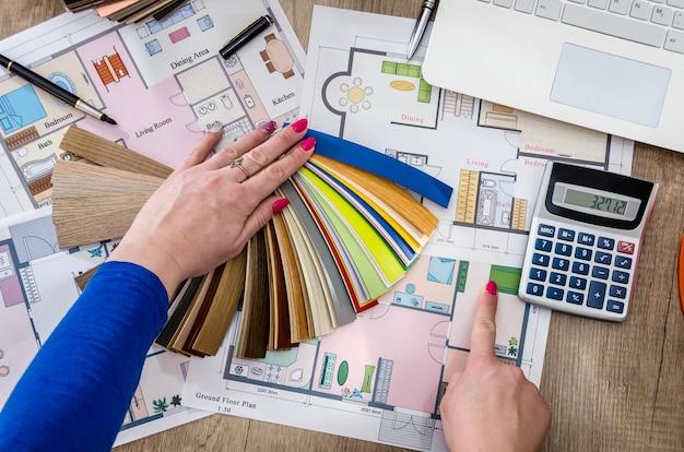 Ręce kobiety z próbkami plastiku i plan domu