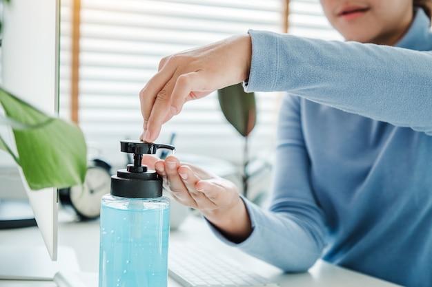 Ręce kobiety za pomocą alkoholu żel czysty środek do dezynfekcji rąk bakterii bakteryjnych i pracy z domu