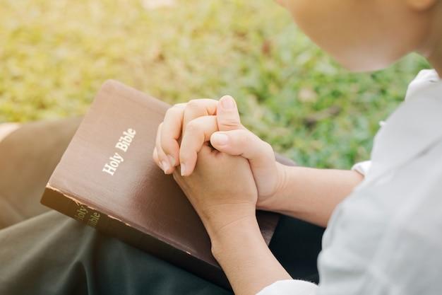Ręce kobiety zaciśnięte w modlitwie nad zamkniętą modlitwą biblijną i dziękuję bogu. tło koncepcji religii chrześcijańskiej.