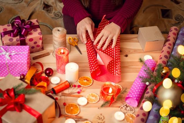 Ręce kobiety, zawijanie prezentu bożonarodzeniowego na drewnianym biurku