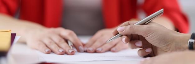 Ręce kolegów z długopisem leżącym na zbliżeniu dokumentów