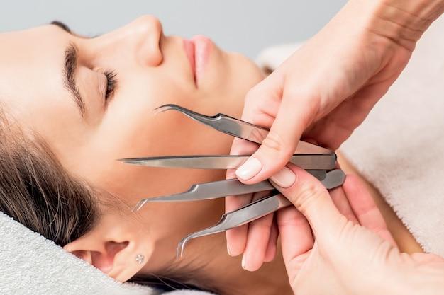 Ręce kosmetolog trzyma pincety do przedłużania rzęs na tle twarzy młodej kobiety, z bliska.