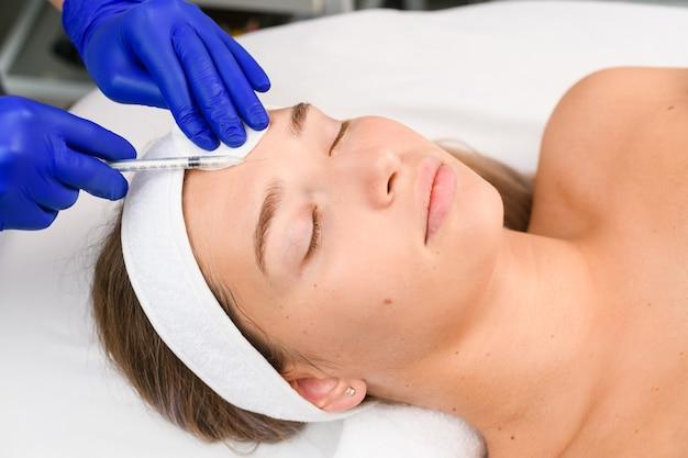 Ręce kosmetologa w niebieskich rękawiczkach trzymają strzykawkę i wypełniają czoło klienta botoksem wypełniającym