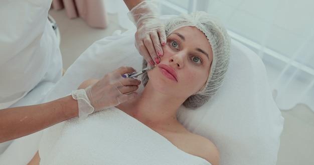 Ręce kosmetyczki wykonują zastrzyki kwasu hialuronowego w dolną wargę dziewczynki. kosmetologia estetyczna. widok z góry.