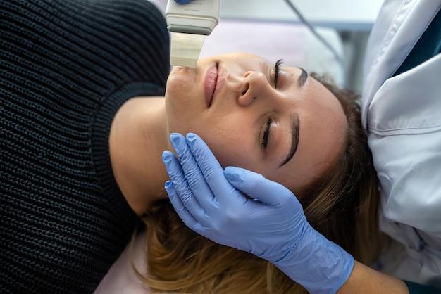 Ręce kosmetyczki za pomocą urządzenia do czyszczenia ultradźwiękowego wykonującego zabieg kobiety w klinice kosmetologicznej