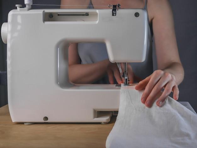 Ręce krawcowe z lnianą tkaniną w procesie pracy maszyny do szycia z organicznej naturalnej tkaniny bawełnianej