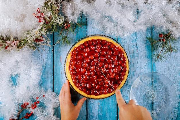 Ręce kroją ciasto wiśniowe na niebieskim drewnianym stole