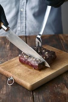 Ręce kroją średnio rzadki gotowany stek z mięsa wieloryba