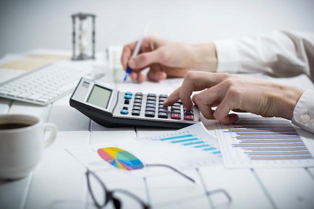 Ręce księgowego pracują na kalkulatorze i przygotowują sprawozdanie finansowe.