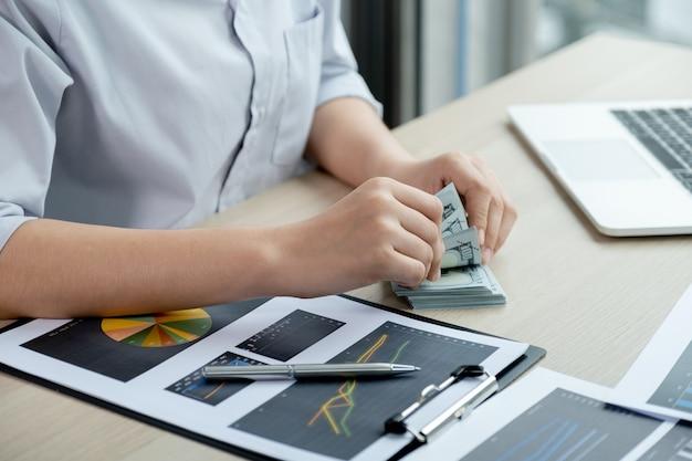 Ręce księgowego przedsiębiorców liczą banknoty dolara i robią konto do płacenia podatku w biurze pracy.