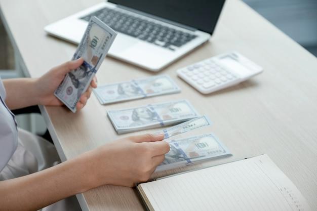 Ręce księgowego przedsiębiorców liczyć banknot dolara do płacenia podatku na białym biurku w biurze pracy.