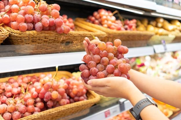 Ręce, które zbierają owoce i warzywa z półki, aby wybrać jakość