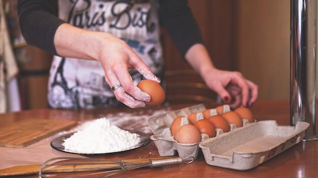 Ręce kucharki zbierającej jajko do wyrabiania ciasta podczas robienia chleba ze stertą pszenicy w pobliżu