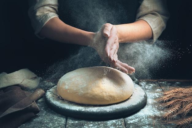 Ręce kucharza posypują ciasto, a chmura mąki fruwa jak kurz.